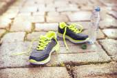 Running shoes and bottle of water — Stock Photo