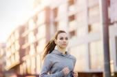 Female runner is jogging in the street — Stok fotoğraf