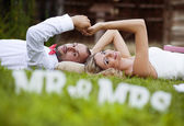 Bride and groom lying on grass — Stock Photo
