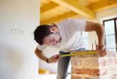 Handyman measuring unfinished room — Stock Photo