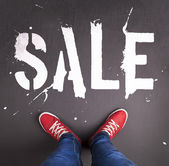 Sale text with red sneakers — Stock Photo