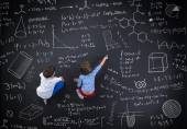 Boy and girl learning in front of a blackboard — Stock Photo