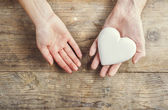 Hands of man and woman holding a heart together — Stock Photo