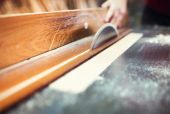 Carpenter's hands cutting wooden planks — Stock Photo