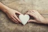 Hands connected through a white heart. — Foto de Stock