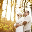 Senior couple hugging in autumn forest — Stock Photo #64497327
