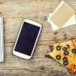 Smart phone, office supplies and pizza — Stock Photo #64575199