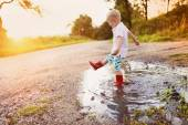 Little boy playing in a puddle — Stock fotografie