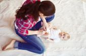 Baby girl getting dressed by her mother — Stock Photo