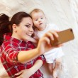 Baby girl and her mother taking selfie — Stock Photo #66976581