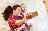 Baby girl and her mother taking selfie — Stock Photo