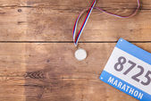 Medal and race number on a floor — Stock Photo