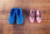 Running shoes and pink court shoes — Stock Photo