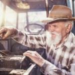 Senior farmer repairing a tractor — Stock Photo #71965757