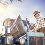 Senior farmer repairing a tractor — Stock Photo #71965763