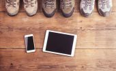 Hiking shoes, smart phone and tablet — Stock Photo
