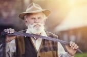 Old farmer with scythe taking a break — Stock Photo