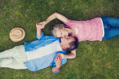 Senior couple lying on a grass and hugging — Stock Photo