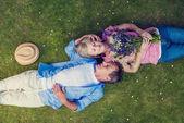 Beautiful senior couple lying on a grass a — Stock Photo