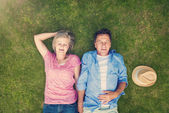Seniors lying on a grass in a park — Stock Photo