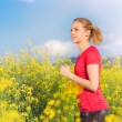 Woman running in spring canola field — Stock Photo #74780181