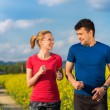 Couple running in spring canola field — Stock Photo #74780297