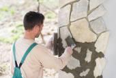 Mason putting decorative stones on a wall — Stock Photo