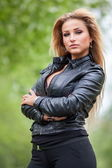 Fashionable young woman in leather jacket outdoors. — Stock Photo