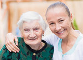 Elderly woman with caregiver — Stock Photo