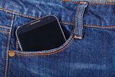 Mobilní telefon a modré džíny — Stock fotografie