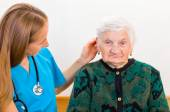 Elderly woman and young doctor — Stock Photo
