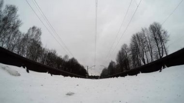 Extreme camera is mounted under the train on the rails. Suburban train passes over the camera. winter shooting — Stock Video