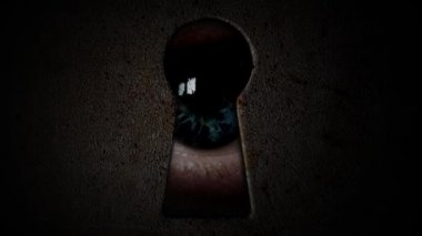Eyes watching through a keyhole. Watch through the dark keyhole — Vídeo stock