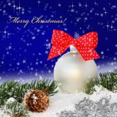 Christmas ball with red bow in the snow — Stock Photo