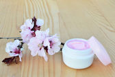 Cosmetic cream with cherry blossoms. — Stock Photo