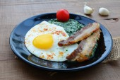 Creamed spinach with fried egg and bacon — Stock Photo