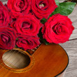 Bouquet of red roses on top of acoustic guitar — Stock Photo #71241899