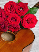 Bouquet of red roses on top of classical guitar — Stock Photo