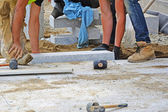Workers laying granite block paver in place. — Stock Photo
