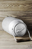 Aluminum old milk can on a wooden background in the vertical format — Stock Photo