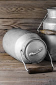 Aluminum old milk cans on a wooden background in the vertical format — Stock Photo