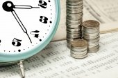 Coins and a clock on a data table — Stock Photo