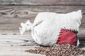 Concept of the thrift storing. Red rice in the burlap sack with the patch on a wooden background — Stock Photo