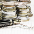 Coins and a fountain pen on charts background — Stock Photo #69338969