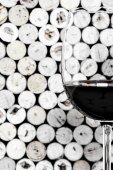 A wine glass on corks background in vertical format — Stock Photo