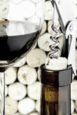 A wine glass, a bottle and a corkscrew on corks background in vertical format — Stock Photo