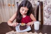 Young small beautiful middle eastern child girl with chocolate cake with pineapple, strawberry, and milk with red dress and dark eyes and long hair happy drinking and eating at home and sitting smiling. looking at camera. studio shot. — Stock Photo