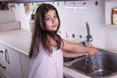 One beautiful middle eastern little girl with pink dress and long dark brown hair and eyes on white kitchen,helping parents to wash dishes and drinking water and smiling looking at camera. — Stock Photo