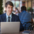 One relaxed young handsome professional businessman working with his laptop, phone and tablet in a noisy cafe. — Stock Photo #81254462