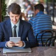 One relaxed young handsome professional businessman working with his laptop, phone and tablet in a noisy cafe. — Stock Photo #81254488